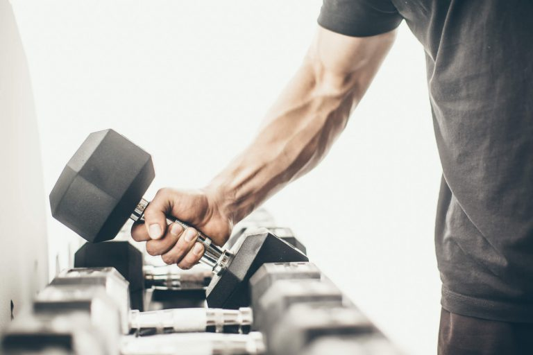 Man's arm lifting dumbell from the rack.
